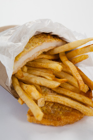 Close-up of french fried chips in a take away paper bag on white background