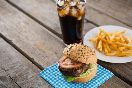 High angle view of hamburger on napkin with french fries in table by drink on table