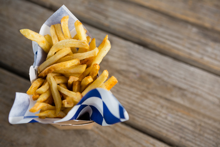 Overhead view of French fries in container on wooden table