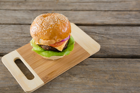High angel view of hamburger with cheese on cutting board at wooden table