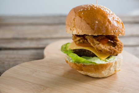 box size: Close up of cheeseburger with onion rings on cutting board