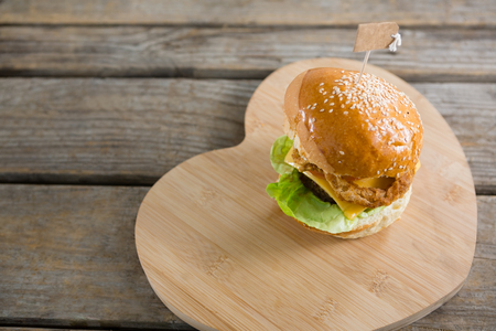 toothpick: High angle view of cheeseburger on heart shape cutting board at wooden table Stock Photo