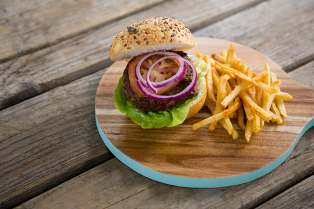 High angle view of hamburger with French fries on cutting board at table