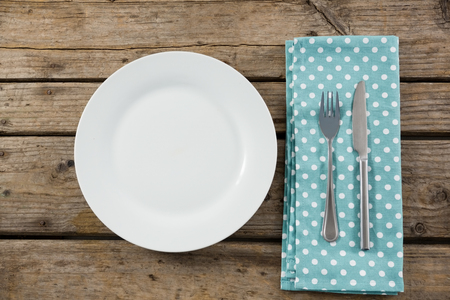 Overhead view of empty plate by napkin and eating utensils on wooden table