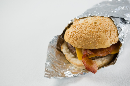 Close up of burger wrapped in foil paper on table