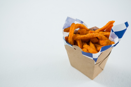 High angke view of spicy French fries in carton box on table