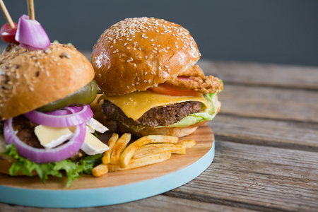 Close up of burgers with french fries on cutting board
