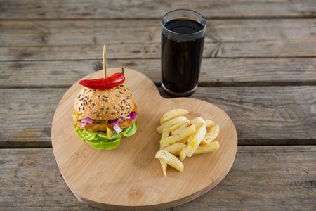 toothpick: High angel view of burger with French fries on heart shape cutting board by drink at wooden table