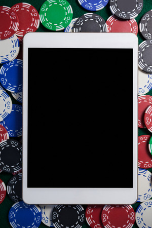 Close-up of digital tablet on multicolored casino chips