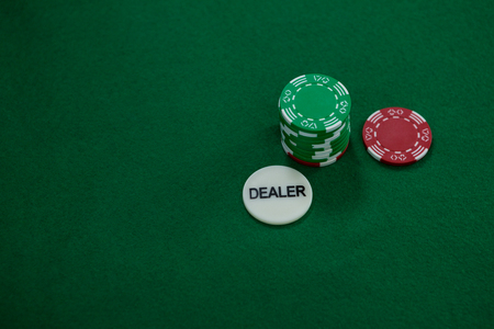 High angle view of dealer coin with chips on green table