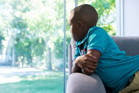 Thoughtful boy looking through window while sitting on sofa at home