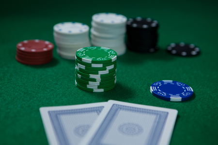 Close-up of chips with cards on green table