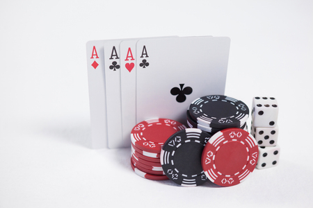 Playing cards, dice and casino chips arranged on white background