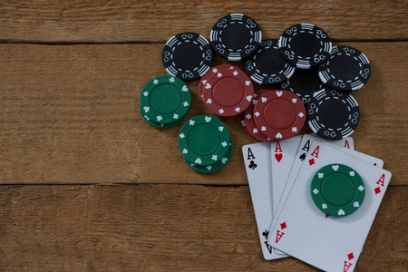 Overhead view of aces and chips on wooden table