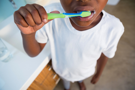 Midsection of boy brushing teeth by sink at bathroom