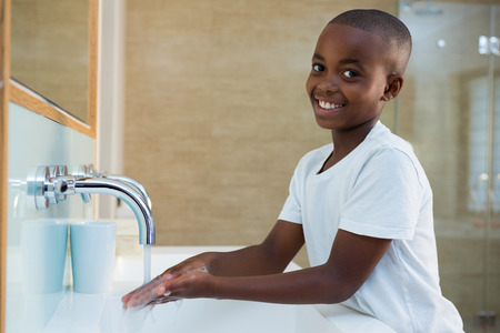 Portrait of smiling boy washing hands in sink at bathroom