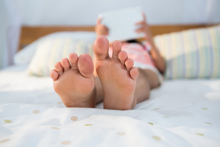 Girl lying on bed while using digital tablet at home
