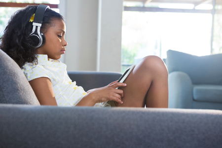 Side view of girl listening music while using tablet computer in living room at home