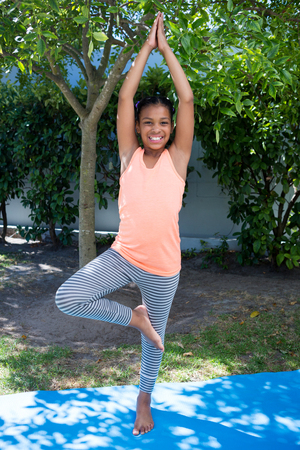 Portrait of smiling girl doing tree pose yoga while exercising in yard