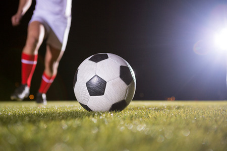 low section: Low section of soccer player and ball on playing field at night