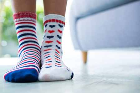 Low section of girl wearing patterned socks while standing at home