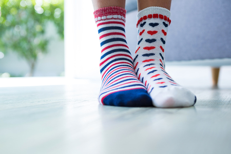 Low section of girl wearing different socks while standing at home Stok Fotoğraf - 81876513