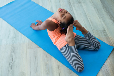 High angle view of girl doing raja bhujangasana while exercising on exercise mat in room