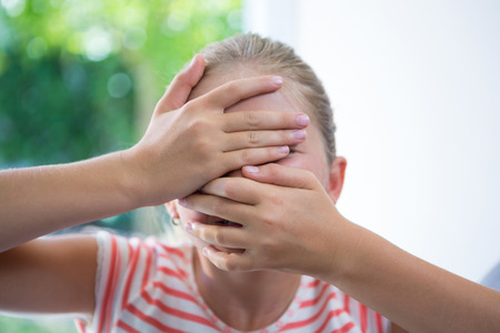 Close up of playful girl covering face while standing by window
