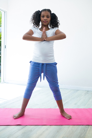 Portrait of girl in prayer position while exercising against wall