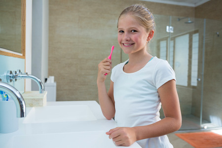 Portrait of girl holding toothbrush while standing in bathroom
