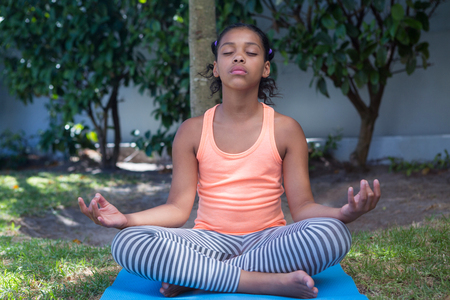 Full length of girl meditating while exercising in yard