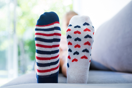 Close up of girl wearing different socks while sitting on sofa at home