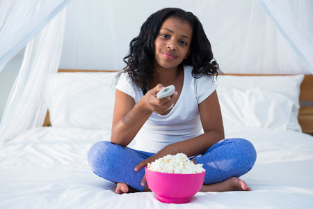 changing channel: Girl holding remote control while watching television in bedroom