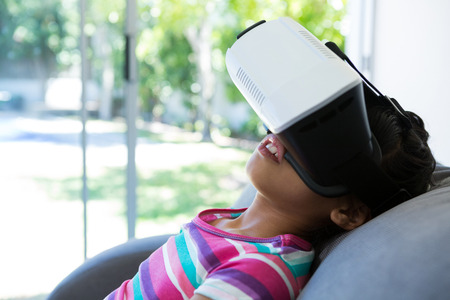 Close up of girl wearing virtual reality simulator while relaxing on sofa at home
