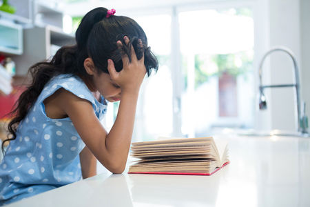 Girl with hand in hair reading novel in kitchen at home