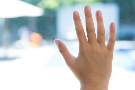 Close up of hand touching glass of window at home