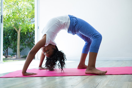 Portrait of girl bending over backwards while exercising in room Stock Photo