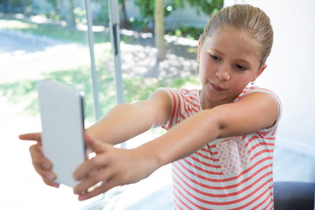 Close up of girl photographing with smartphone while standing at home Stock Photo