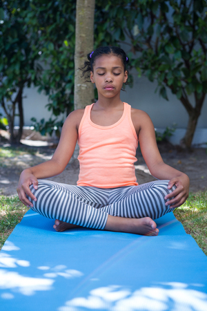 Girl meditating while exercising in yard Stock Photo