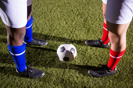 Low section of players standing by soccer ball on playing field at night Stock Photo