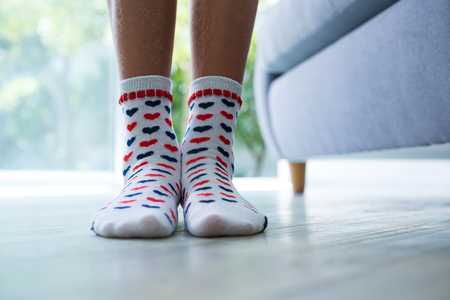 Low section of girl wearing socks while standing by sofa at home Stock Photo