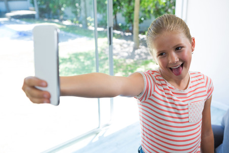 Playgul giirl taking selfie while standing by window at home
