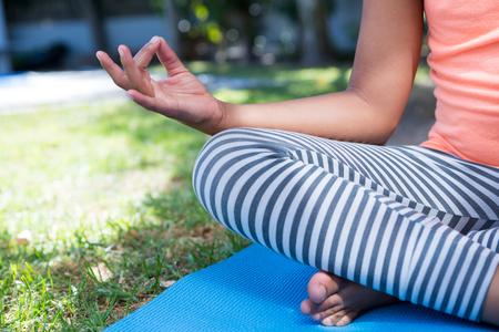 Cropped image of girl meditating while exercising in yard