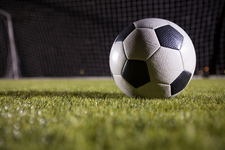 Close-up of soccer ball on playing field against goal post