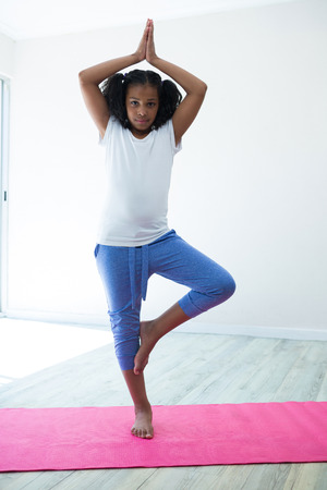 Portrait of girl doing tree pose yoga while exercising against wall in room Stock Photo
