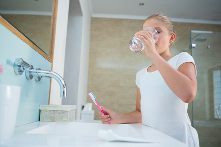 Girl drinking water while holding toothbrush by sink in bathroom