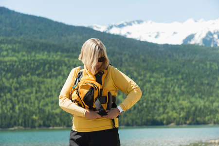 Mature woman wearing life jacket while standing against mountain LANG_EVOIMAGES