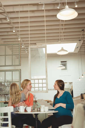 desirable: Pregnant woman and friend interacting with each other in restaurant LANG_EVOIMAGES