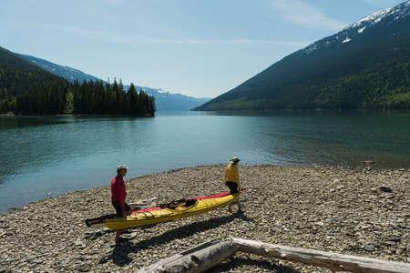 Couple carrying kayak while walking lakeshore against sky