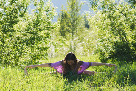 Woman doing stretching exercise in forest on a sunny day